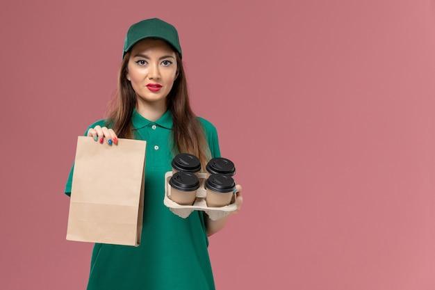Vooraanzicht vrouwelijke koerier in groen uniform en cape met voedselpakket en bezorging koffiekopjes op roze bureau service uniform bezorgbedrijf