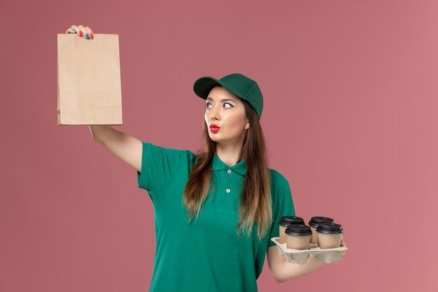 Vooraanzicht vrouwelijke koerier in groen uniform en cape met voedselpakket en bezorging koffiekopjes op roze bureau service uniforme levering baan werk