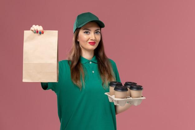 Vooraanzicht vrouwelijke koerier in groen uniform en cape met voedselpakket en bezorgkoffiekopjes op de roze baliedienst uniforme bezorgopdracht