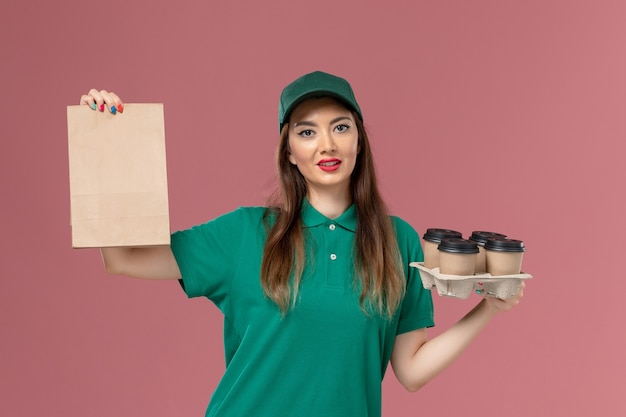 Vooraanzicht vrouwelijke koerier in groen uniform en cape met voedselpakket en levering koffiekopjes op roze bureau service uniforme levering baan meisje