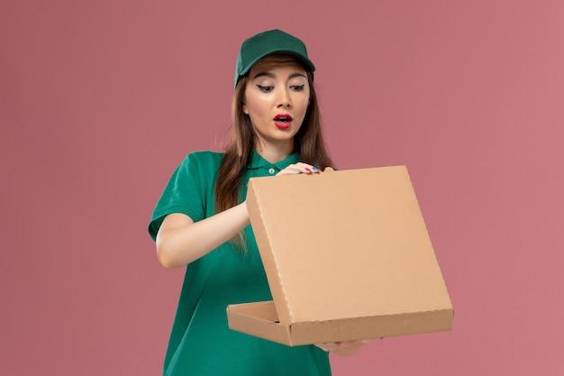 Vooraanzicht vrouwelijke koerier in groen uniform houden en openen van voedselleveringsdoos op roze muurdienst uniform bezorgingsmeisje