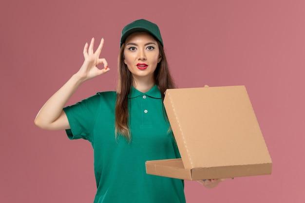 Vooraanzicht vrouwelijke koerier in groen uniform met een lege voedselleveringsdoos op roze muur service uniform bezorgingsmeisje bedrijf