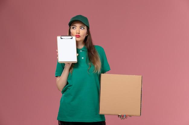 Vooraanzicht vrouwelijke koerier in groen uniform met notitieblok voor voedseldoos en denken aan de roze muur