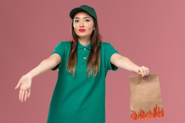 Vooraanzicht vrouwelijke koerier in groen uniform met papieren voedselpakket op de lichtroze muurservice uniforme levering