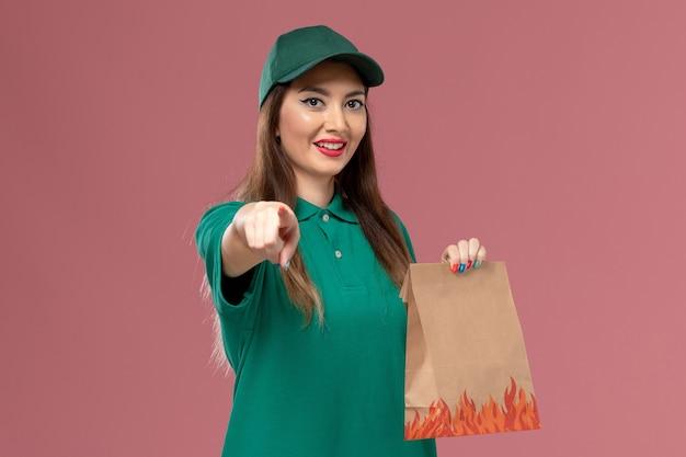 Vooraanzicht vrouwelijke koerier in groen uniform met papieren voedselpakket op de roze muur service uniforme levering