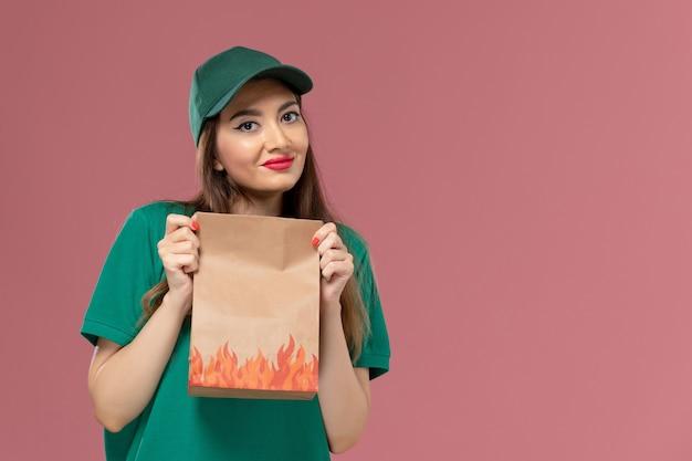 Vooraanzicht vrouwelijke koerier in groen uniform met papieren voedselpakket op de roze muur