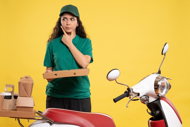 Vooraanzicht vrouwelijke koerier in groen uniform met pizzadoos op gele achtergrond servicemedewerker baanbezorging werk eten