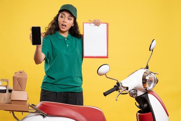 Vooraanzicht vrouwelijke koerier in groen uniform met telefoon en bestandsnotitie op de gele achtergrond servicemedewerker baanbezorging werk eten