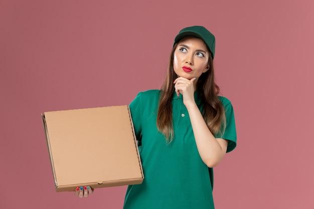 Vooraanzicht vrouwelijke koerier in groen uniform met voedseldoos denken over lichtroze muur baan werknemer service uniforme levering