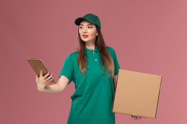 Vooraanzicht vrouwelijke koerier in groen uniform met voedseldoos en blocnote op de roze muur