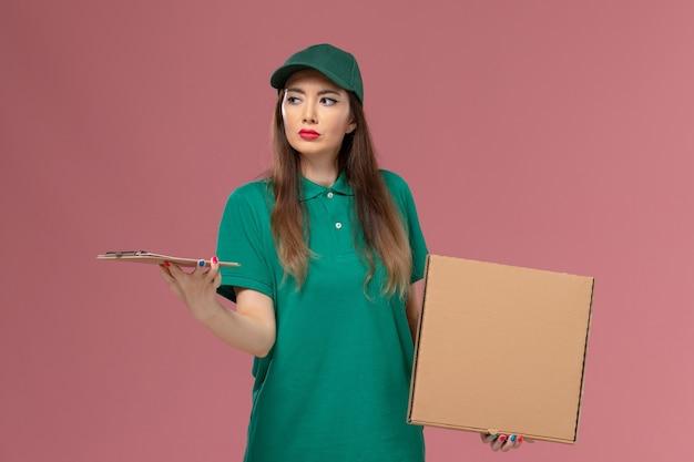 Vooraanzicht vrouwelijke koerier in groen uniform met voedseldoos en blocnote op lichtroze muur bedrijf dienst werknemer uniforme levering baan