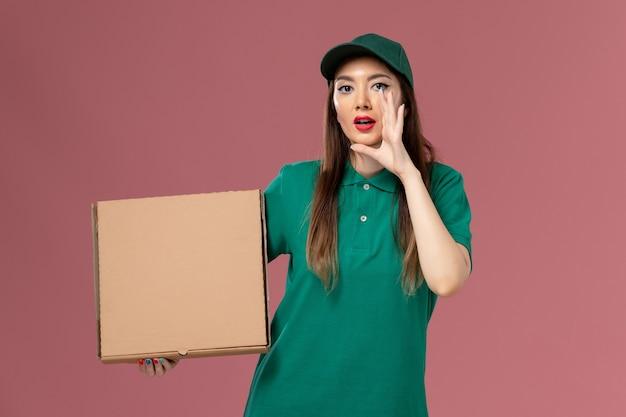 Vooraanzicht vrouwelijke koerier in groen uniform met voedseldoos fluisteren op roze muur baan service uniforme levering