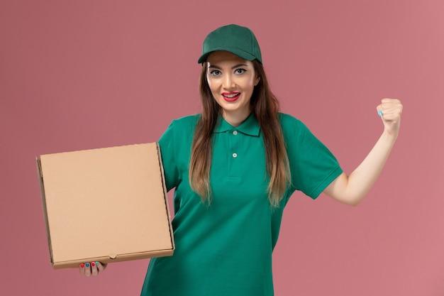 Vooraanzicht vrouwelijke koerier in groen uniform met voedseldoos juichen op lichtroze muur job werknemer service uniforme levering