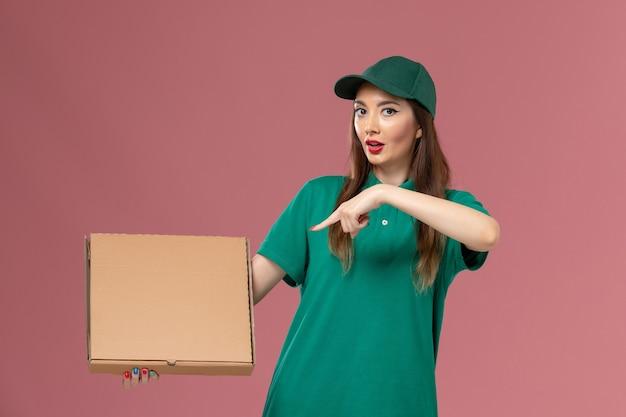 Vooraanzicht vrouwelijke koerier in groen uniform met voedseldoos op de roze muur