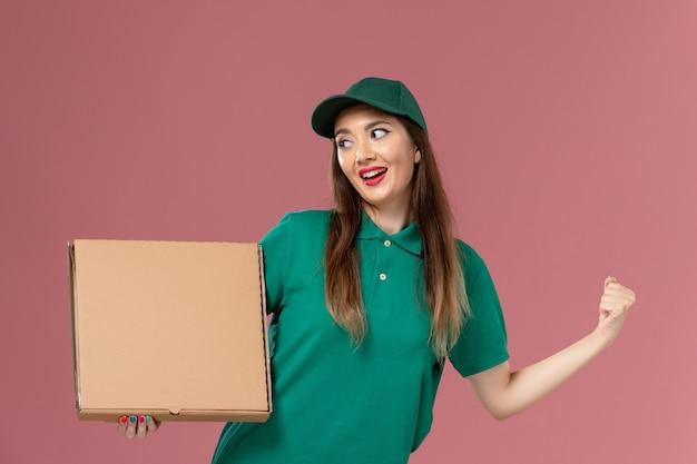 Vooraanzicht vrouwelijke koerier in groen uniform met voedseldoos op het lichtroze bureau werker uniforme levering