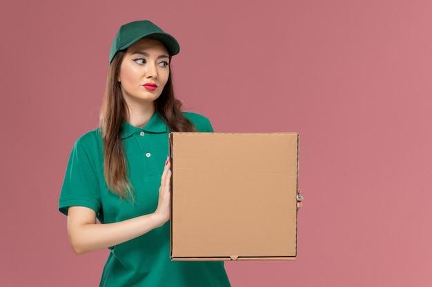 Vooraanzicht vrouwelijke koerier in groen uniform met voedseldoos op lichtroze muur baan service uniform leveringswerk