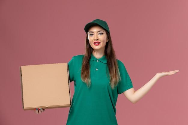 Vooraanzicht vrouwelijke koerier in groen uniform met voedseldoos op lichtroze muur job werknemer service uniforme levering