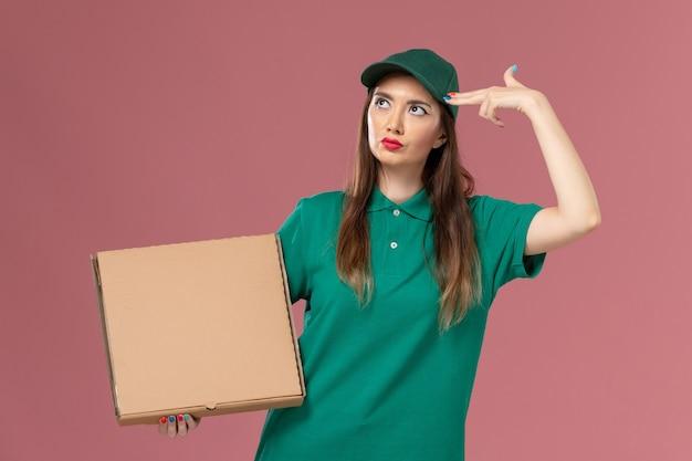 Vooraanzicht vrouwelijke koerier in groen uniform met voedseldoos poseren op lichtroze muur job werknemer service uniforme levering