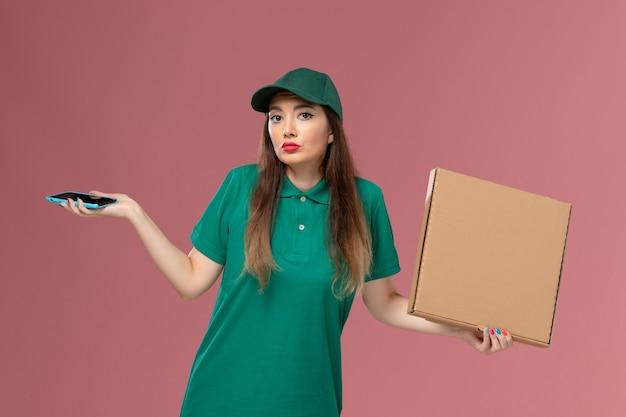 Vooraanzicht vrouwelijke koerier in groen uniform met voedselleveringsdoos en telefoon op lichtroze muur