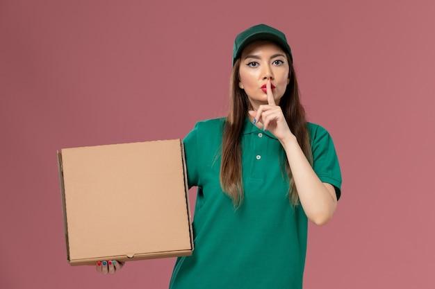 Vooraanzicht vrouwelijke koerier in groene uniforme voedseldoos houden op de lichtroze muur job service uniforme levering