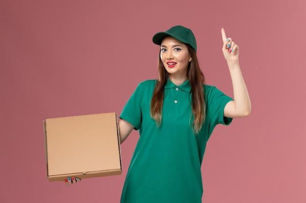 Vooraanzicht vrouwelijke koerier in groene uniforme voedseldoos op roze muur baan service uniform bezorgbedrijf