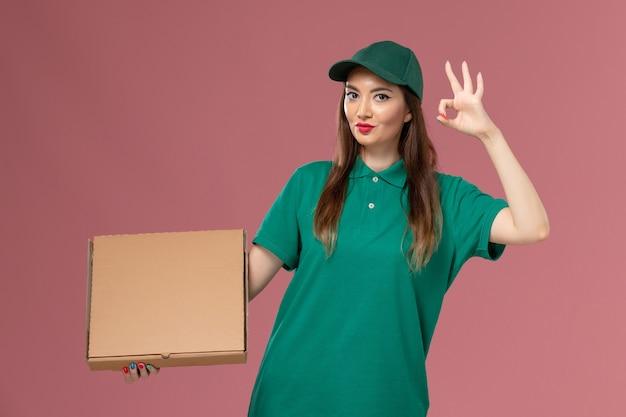 Vooraanzicht vrouwelijke koerier in groene uniforme voedseldoos op roze muur baan service uniform leveringswerk