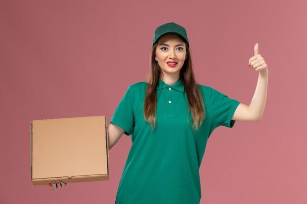 Vooraanzicht vrouwelijke koerier in groene uniforme voedseldoos op roze muur baan service uniforme bezorger