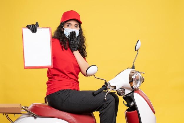 Vooraanzicht vrouwelijke koerier in masker met bestandsnotitie op gele achtergrond covid- baan uniform servicewerk pandemische levering