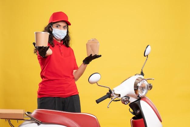 Vooraanzicht vrouwelijke koerier in masker met bezorgingsdessert en voedsel op gele achtergrond covid- baan uniforme werknemer dienstverlening