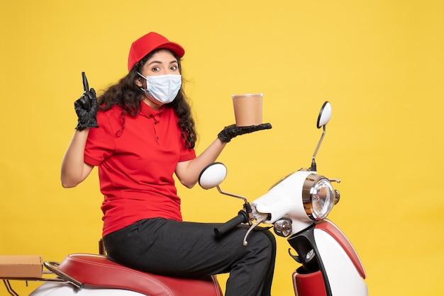 Vooraanzicht vrouwelijke koerier in masker met bezorgingsdessert op geel bureau covid- baan uniforme werknemer service pandemische levering