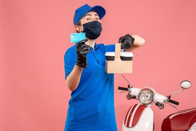 Vooraanzicht vrouwelijke koerier in masker met bezorgkoffie en bankkaart op roze Gratis Foto
