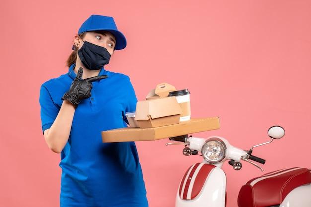 Vooraanzicht vrouwelijke koerier in masker met bezorgkoffie en eten op roze vloer pandemische covid-uniforme baandienstmedewerker levering