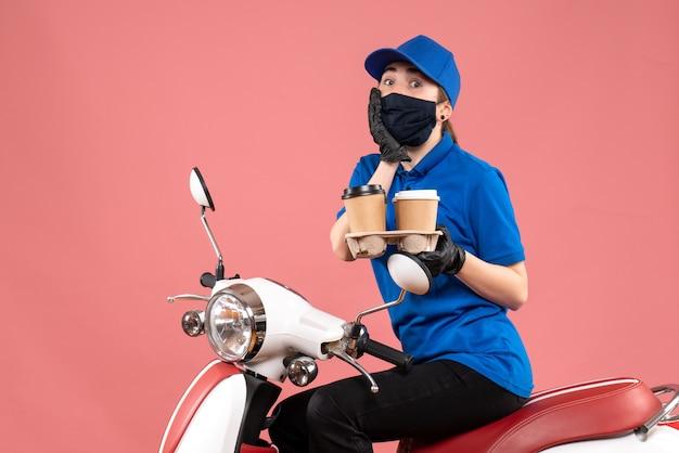 Vooraanzicht vrouwelijke koerier in masker met bezorgkoffie op het roze