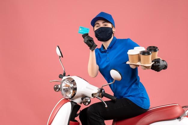 Vooraanzicht vrouwelijke koerier in masker met koffie en bankkaart op roze