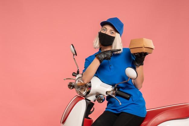 Vooraanzicht vrouwelijke koerier in masker met weinig voedselpakket op roze