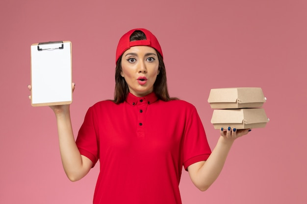 Vooraanzicht vrouwelijke koerier in rode uniform cape met blocnote en kleine bezorgvoedselpakketten op haar handen op lichtroze muur, dienstverlener