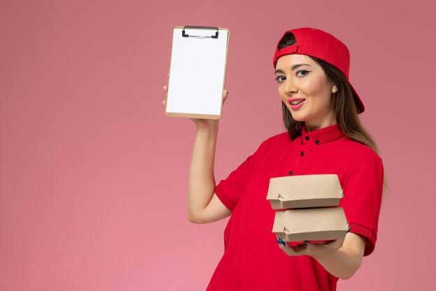 Vooraanzicht vrouwelijke koerier in rode uniform cape met blocnote en kleine bezorgvoedselpakketten op haar handen op lichtroze muur, werkdienstbezorgster