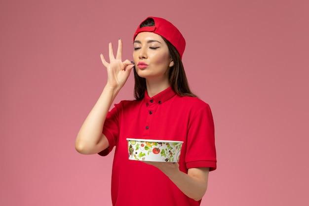 Vooraanzicht vrouwelijke koerier in rode uniforme cape met bezorgkom op haar handen op lichtroze muur, uniforme bezorgmedewerker