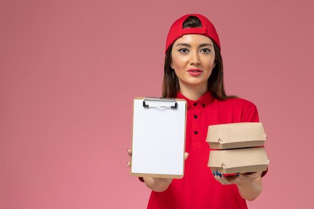 Vooraanzicht vrouwelijke koerier in rode uniforme cape met blocnote en kleine bezorgvoedselpakketten op haar handen op lichtroze muur, baan voor dienstverlener