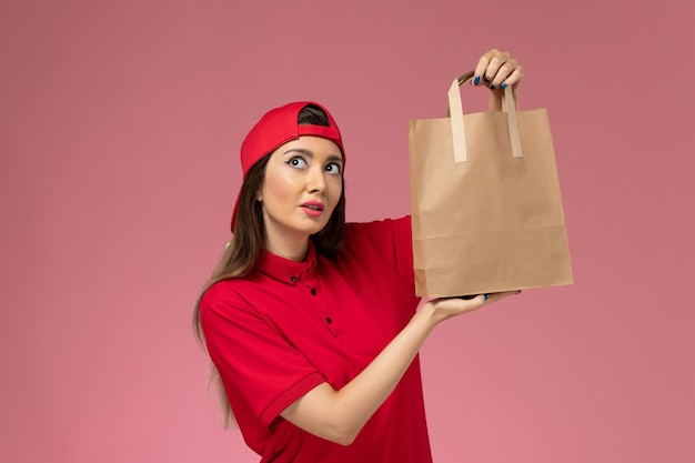 Vooraanzicht vrouwelijke koerier in rode uniforme cape met leveringsdocument pakket op haar handen op de roze muur, uniforme baan van de bezorger