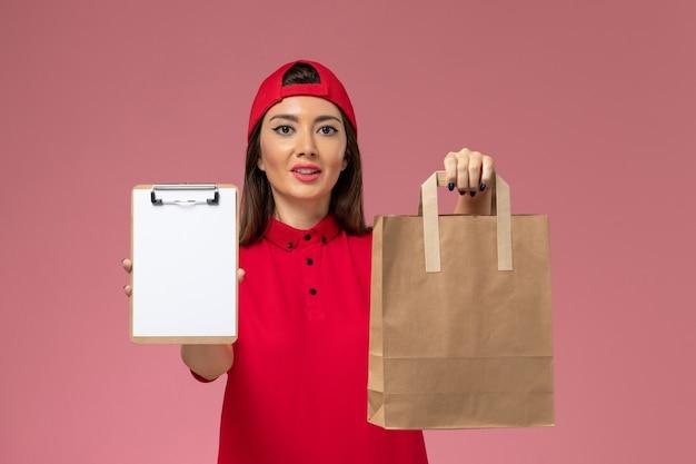 Vooraanzicht vrouwelijke koerier in rode uniforme cape met papieren bezorgpakket en blocnote op haar handen op de roze muur, uniforme bezorger baan