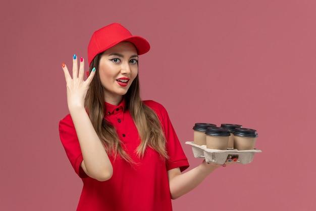 Vooraanzicht vrouwelijke koerier in rood uniform bedrijf levering koffiekopjes met haar nagels op de roze achtergrond service levering baan uniforme werknemer