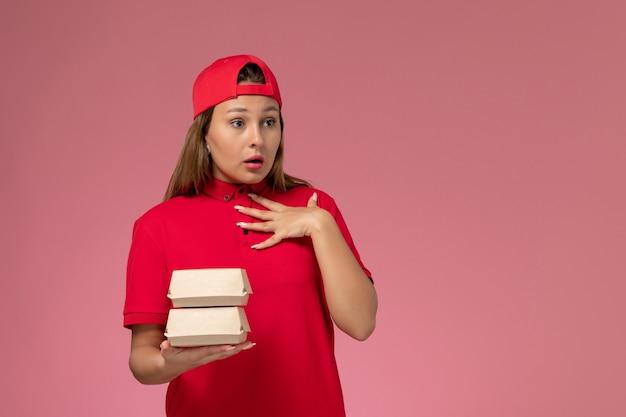 Vooraanzicht vrouwelijke koerier in rood uniform en cape bedrijf levering voedselpakket op lichtroze achtergrond uniforme bezorgdienst bedrijf baan werk