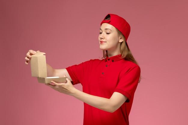 Vooraanzicht vrouwelijke koerier in rood uniform en cape die een klein leeg leveringsvoedselpakket op roze muur, eenvormig bezorgbedrijf vasthouden en openen