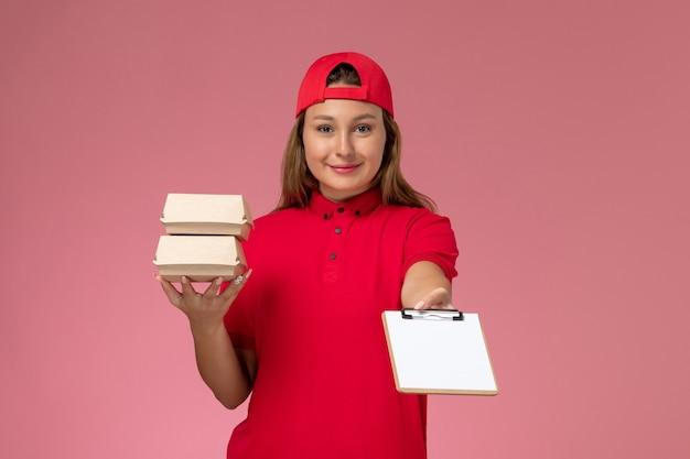 Vooraanzicht vrouwelijke koerier in rood uniform en cape die kleine bezorgingsvoedselpakketten op de lichtroze muur houdt, uniforme werkbezorgservice