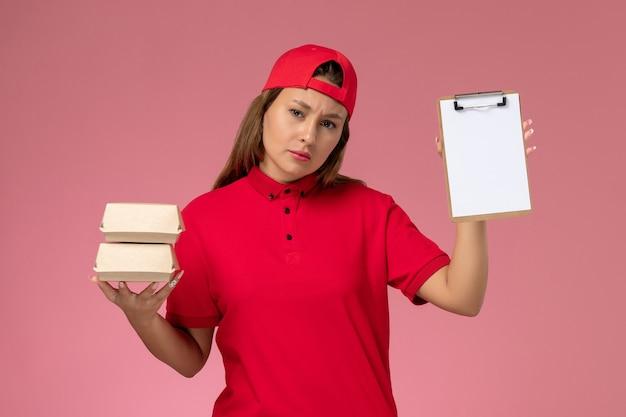 Vooraanzicht vrouwelijke koerier in rood uniform en cape die kleine bezorgvoedselpakketten blocnote op lichtroze muur, uniforme baanbezorgingsmedewerker houdt