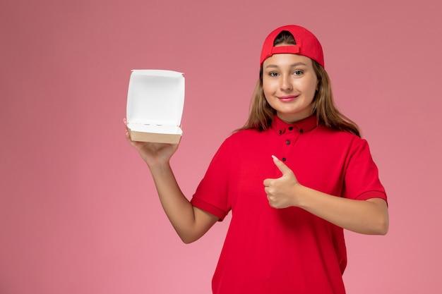 Vooraanzicht vrouwelijke koerier in rood uniform en cape die leeg bezorgingsvoedselpakket op de lichtroze muur houdt, uniform bezorgbedrijf