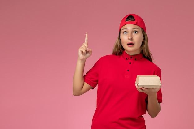 Vooraanzicht vrouwelijke koerier in rood uniform en cape die voedselpakket voor bezorging houden en denken aan roze muur, uniforme baanmedewerker van het bezorgbedrijf