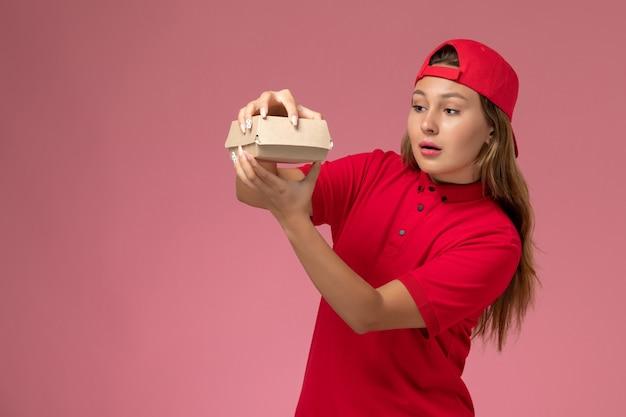 Vooraanzicht vrouwelijke koerier in rood uniform en cape die voedselpakket voor bezorging vasthoudt en opent op de roze muur, baan voor uniform bezorgbedrijf
