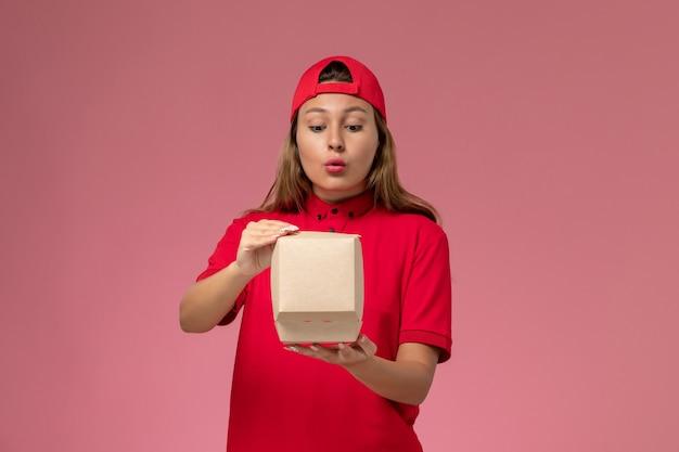 Vooraanzicht vrouwelijke koerier in rood uniform en cape die voedselpakket voor bezorging vasthoudt en opent op lichtroze muur, uniforme bezorgdienst baan werknemer bedrijf